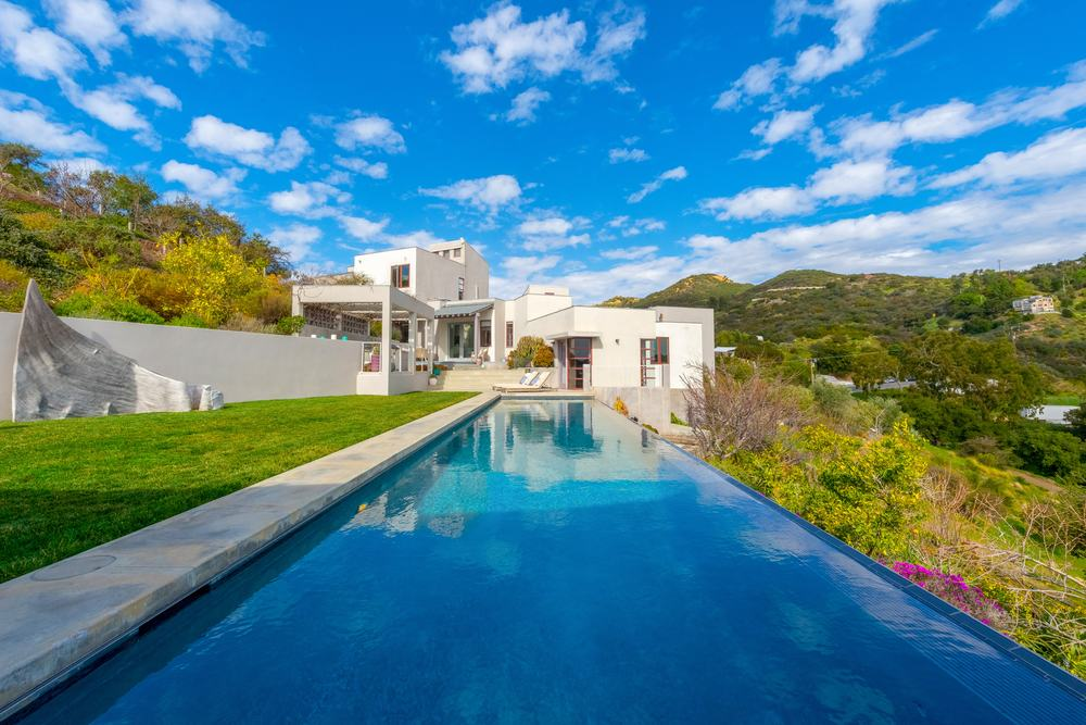 This beautiful cubist home has a large infinity pool at the back with a wonderful view of the surrounding green landscape that gives a lovely background contrast for the straight lines and cube structures of the beige house. Images courtesy of Toptenrealestatedeals.com.