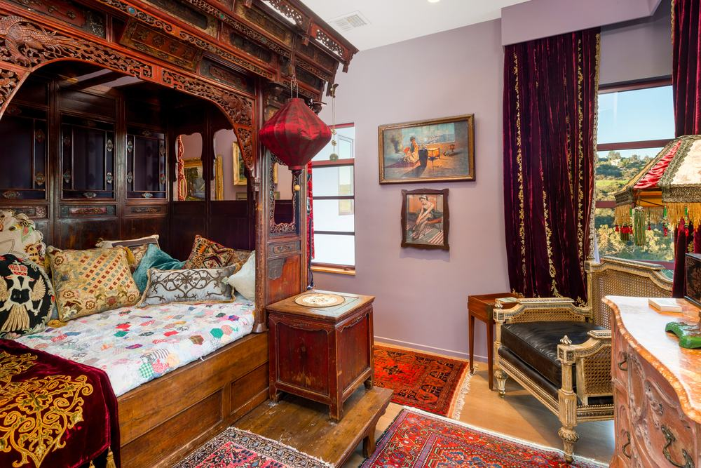 This gorgeous and charming bedroom has a large wooden structure that has an antique and oriental feel to its design. This creates a charming cove for the small bed paired with a cushioned arm chair on the corner for a reading nook. Images courtesy of Toptenrealestatedeals.com.