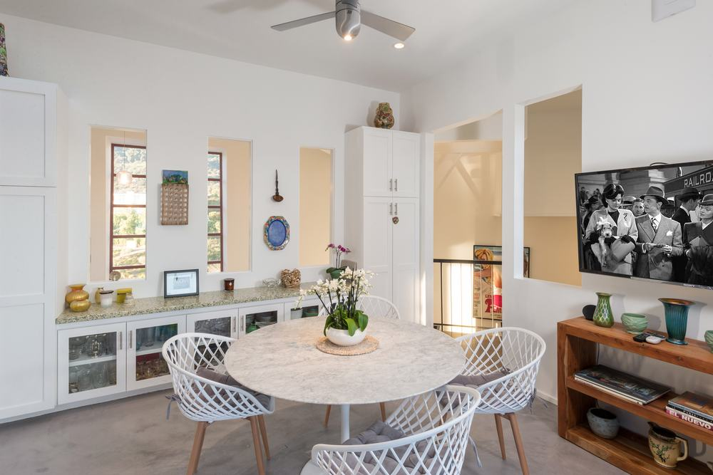 The homey dining room has a simple wooden round table surrounded by white woven chairs topped with a modern ceiling fan from the white ceiling. Images courtesy of Toptenrealestatedeals.com.