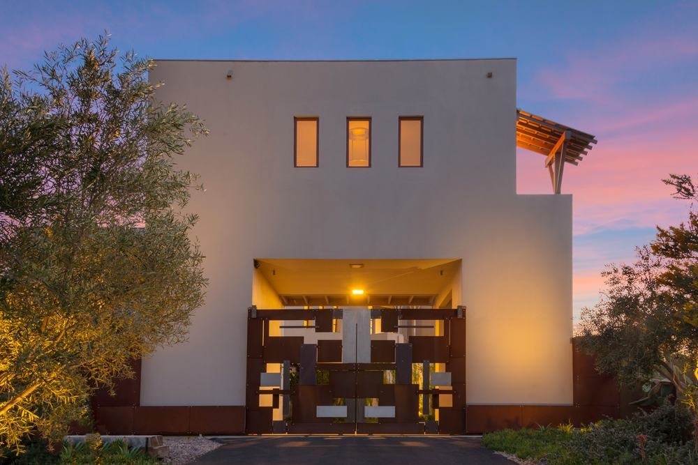 This is a closer look at the main gate of the house with a dark brown tone complemented by the beige exterior walls and the warm yellow exterior lights. Images courtesy of Toptenrealestatedeals.com.