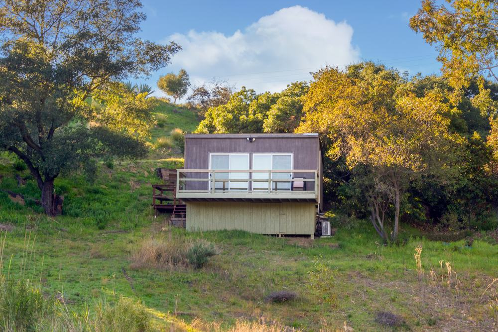 This is the separate guest house with the same cubist style as the main house. It has simple exteriors that makes it stand out against the surrounding lush green landscape with tall trees. Images courtesy of Toptenrealestatedeals.com.