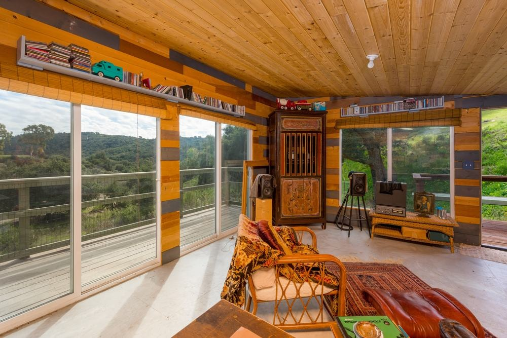 This is the interior of the guest house featuring a large open room bathed in natural lights from the surrounding glass doors that complement the wooden ceiling. Images courtesy of Toptenrealestatedeals.com.
