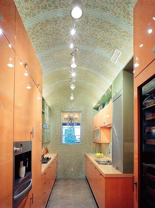 Handcrafted glass tiles in a high vaulted roof make this kitchen special and imaginative. This orange cookroom kitchen arranged toward the finish of a room was made to look open in light of its roof.