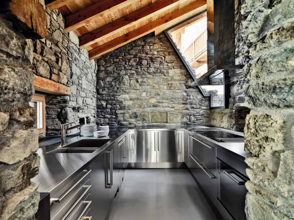 This kitchen is stylish with its stone walls and wooden roof with beams. The stainless steel pieces of equipment, alongside the gray flooring, are simply perfect together.