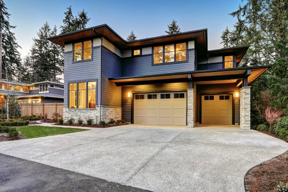 Luxury modern home with blue siding and natural stone wall trim.