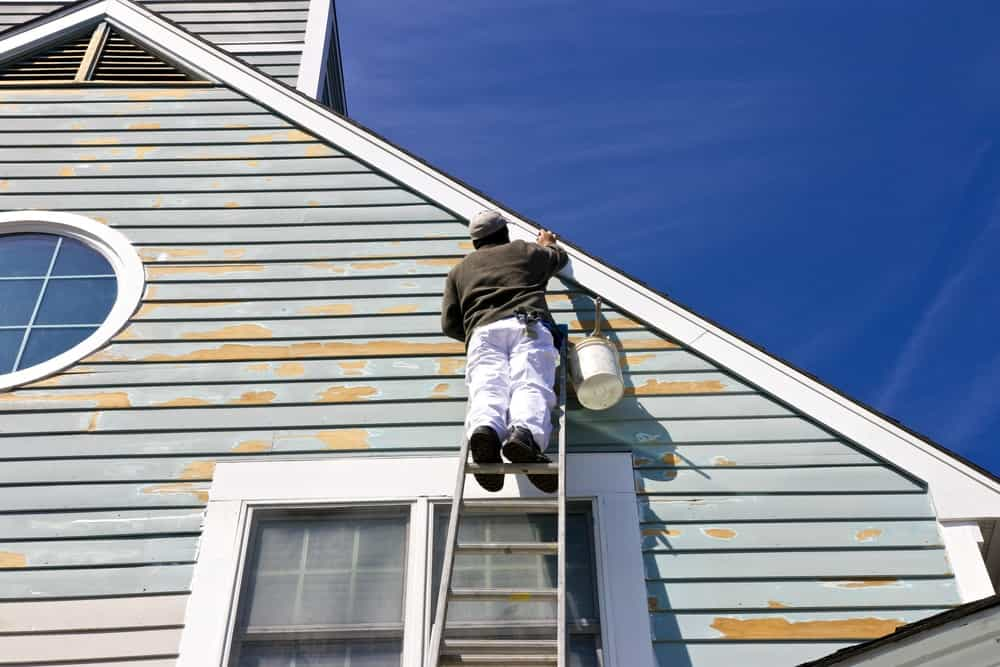 A worker on a ladder doing house exterior paint work.