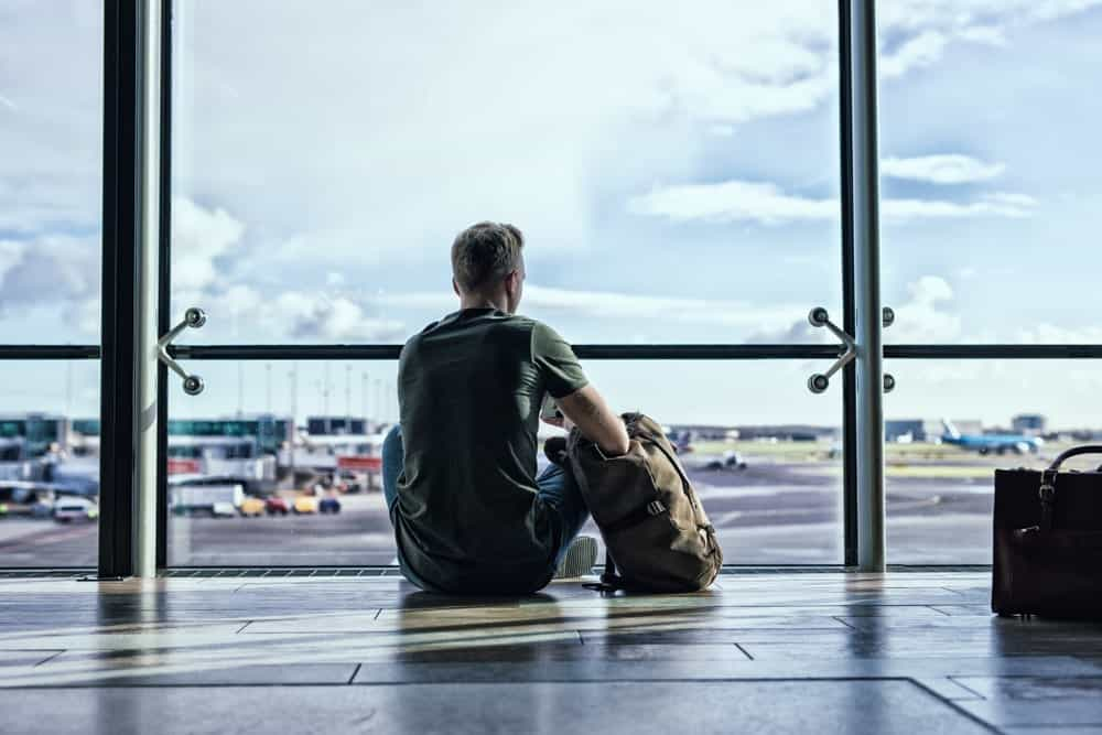 Lone man sitting in the airport and looking out the windows.