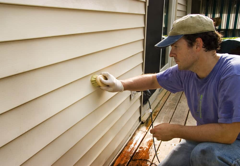 Man washing a home's exterior siding.