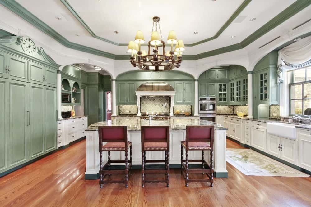 This is a bright spacious kitchen with green accents to its tray ceiling and surrounding cabinetry that are complemented by the white arches and columns.