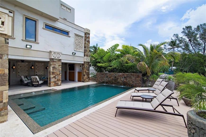 The view of a stunning swimming pool features a light wood deck where cushioned loungers sit.