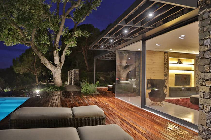 Sharp overhangs provide shade and night lighting for the deck, as they ease the transition from indoors to out.