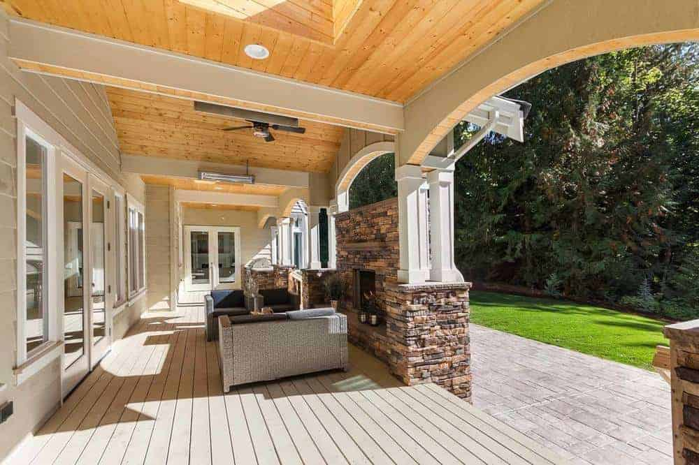 This large outdoor area is warmed by the stone fireplace that blends well with the stone base of the flanking white pillars.