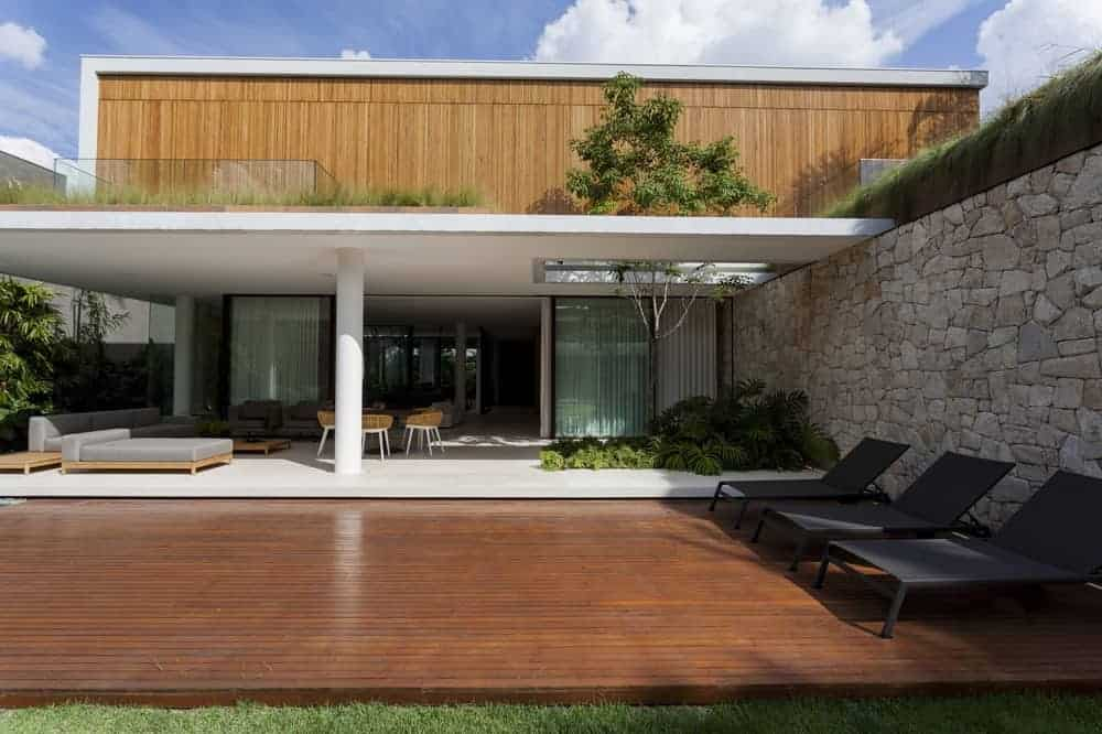 This large poolside area has a dark wooden flooring paired with a few lawn chairs facing the pool shaded by the large white stone wall behind.