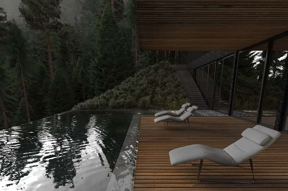 This is a view from the wooden flooring of the poolside that has comfortable lawn chairs facing the pool and the forest view beyond.