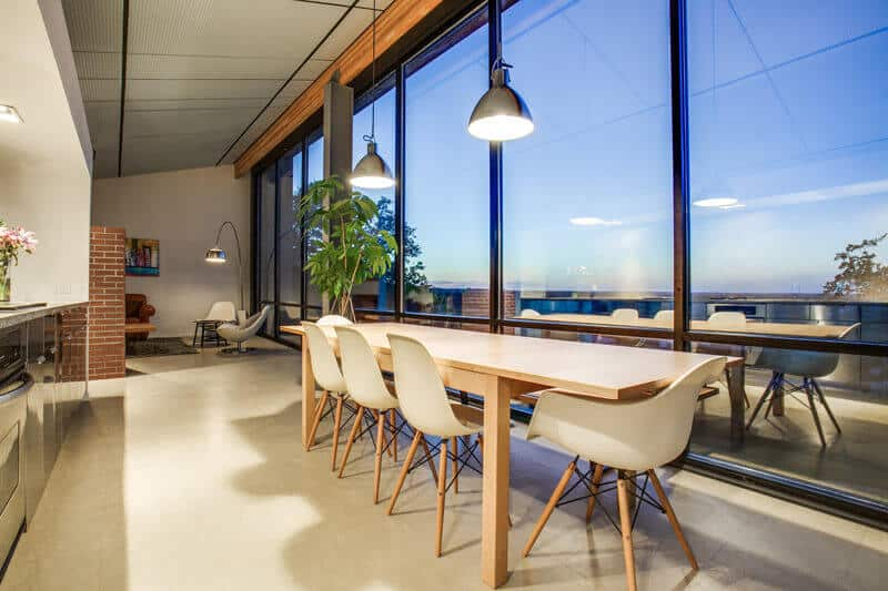 The long dining table in the kitchen offers a great view of the backyard and a perfect place to guests to sit, relax, and watch the preparations while entertaining.