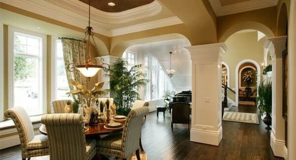 This dining area with a small round dining table with a cozy seat on the dark hardwood flooring.