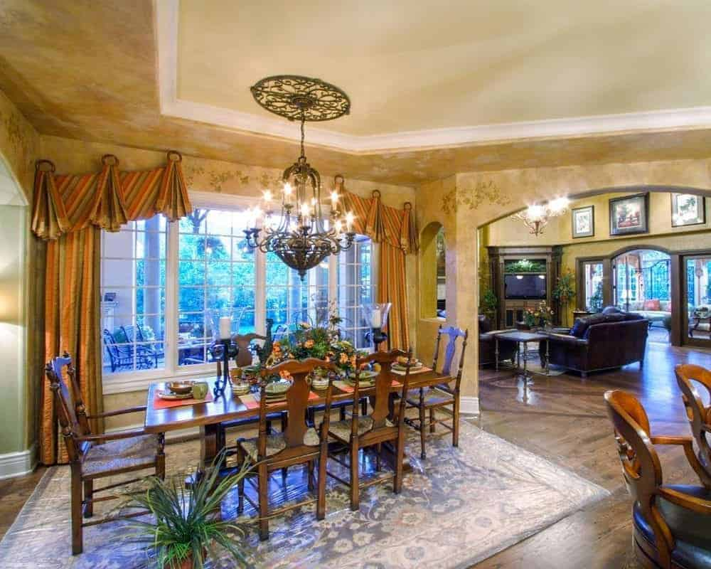 The dining area has a wooden table and chairs on the rug and lit by brilliant candle chandelier.