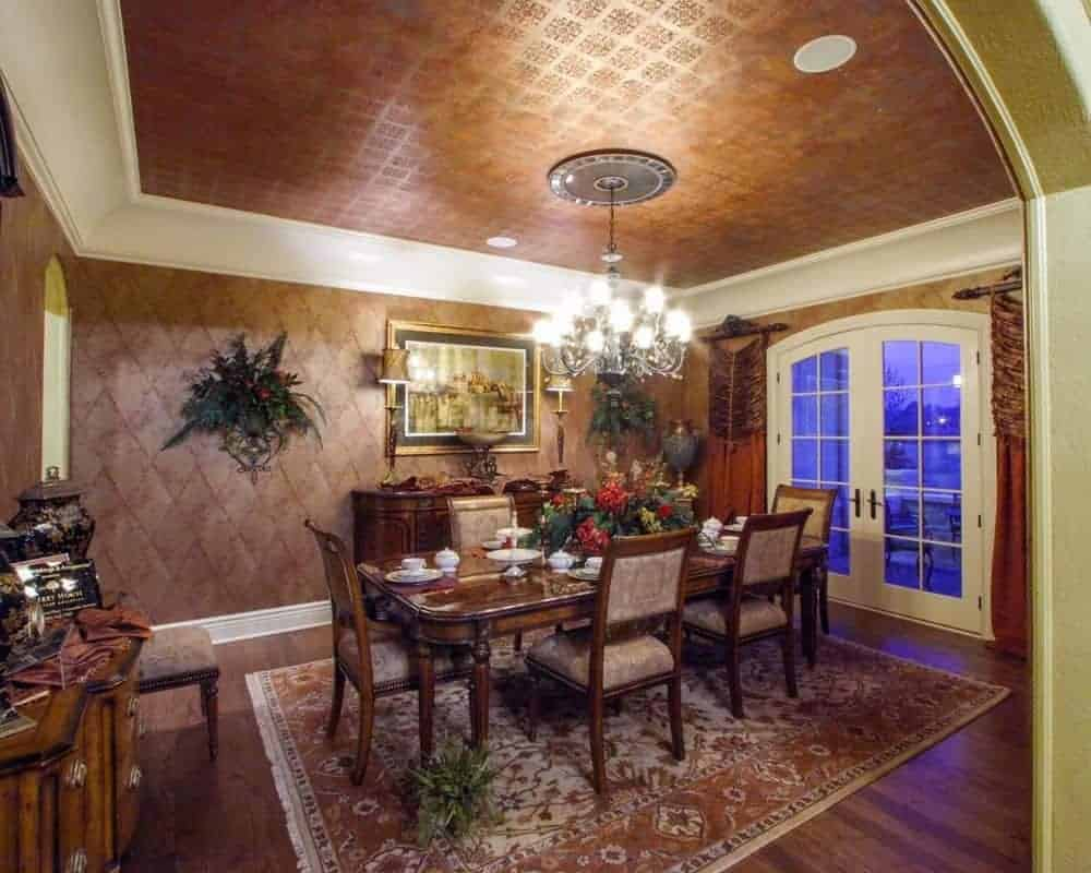 A formal dining room highlighting a dark wooden table set on the carpet. It also has wooden furniture and impressive chandeliers.