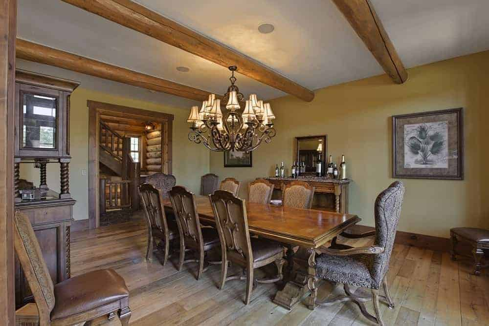 The beautiful dining room has a large wooden rectangular dining table topped with a charming chandelier that hangs from one of the exposed wooden log beams of the ceiling.