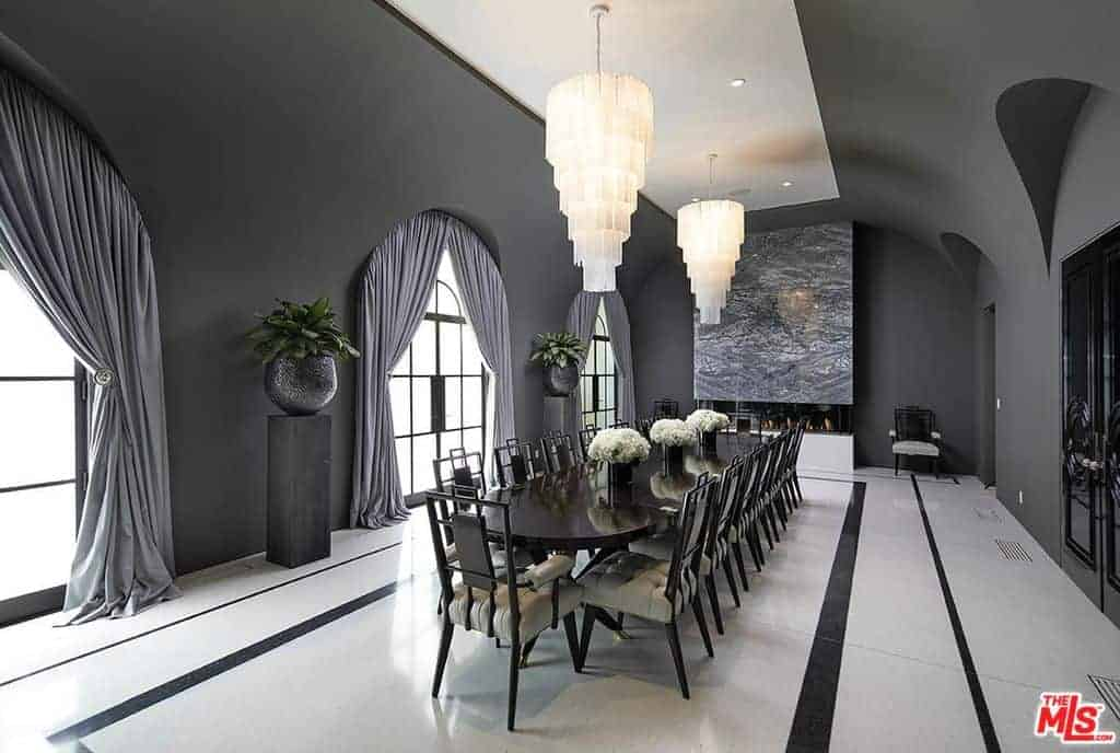 A dining room fit for royalty that is absolutely huge, but also stylish in a modern glam style. The custom black and white floor matches the dark gray walls and white ceiling.