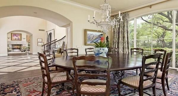 This formal dining room features the round dining set on the rug lit by can stunning candle chandelier.