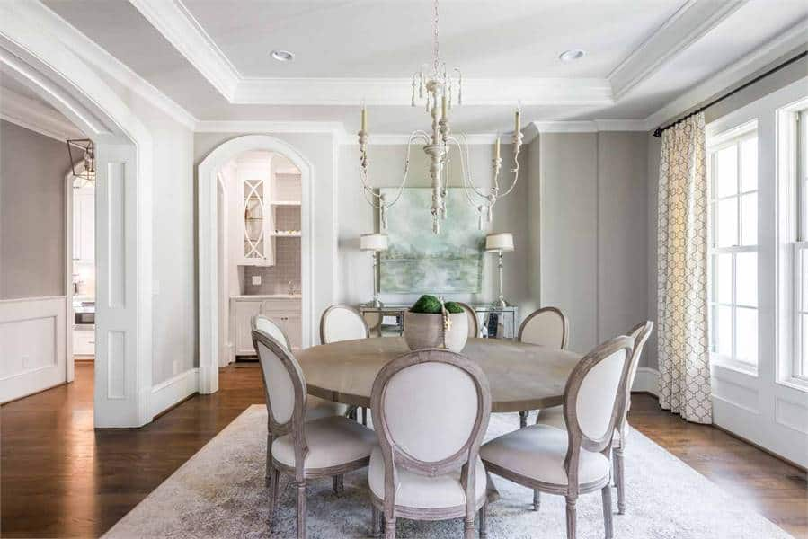 This dining room has a round dining table with gray chairs on the stylish rug. It also has hardwood flooring and candle chandelier.