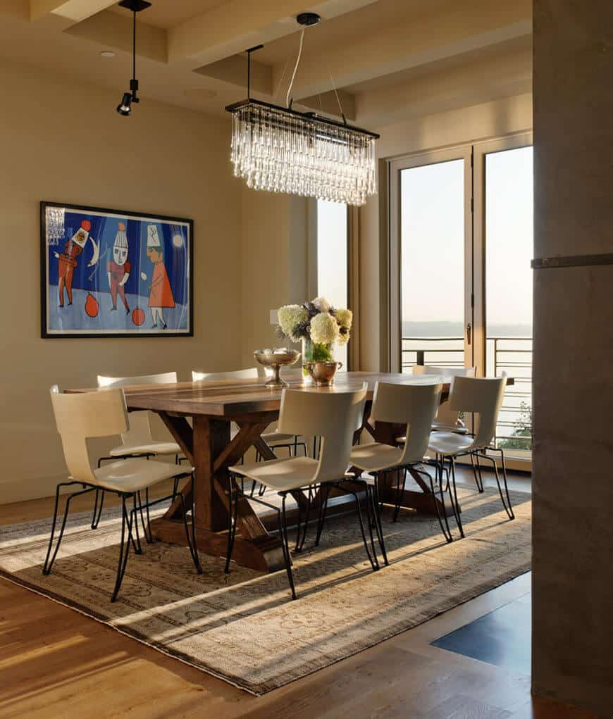The dining room centers a large all-wood rustic styled table over a patterned area rug, surrounded by sleekly modern white chairs.