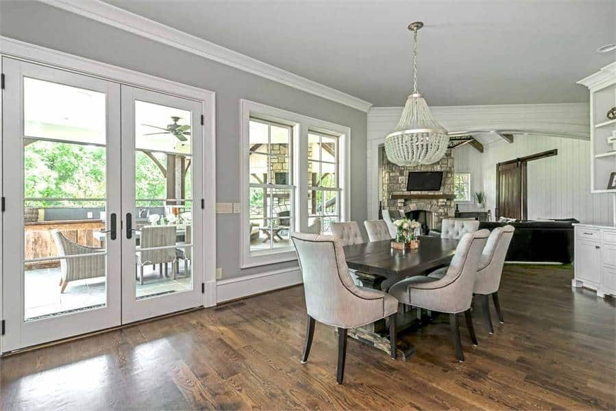 This dining area has a rectangular dining table with a comfy chair on the hardwood flooring. It also has a gorgeous chandelier and a door that leads to the balcony.