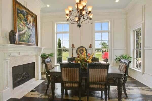 This formal dining room features dark wooden dining set lit by a stunning chandelier and it also had a fireplace and landscape painting on top.