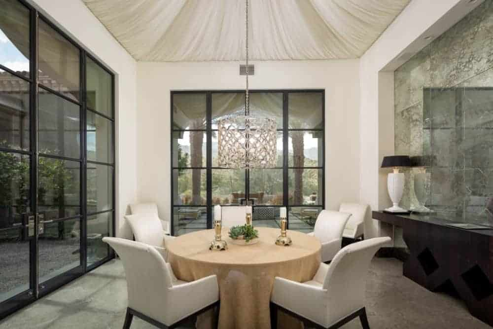 This dining room has a circular table with chairs lightens by a gorgeous chandelier hanging in the high vaulted ceiling. It also has a glass sliding door leading to the balcony.