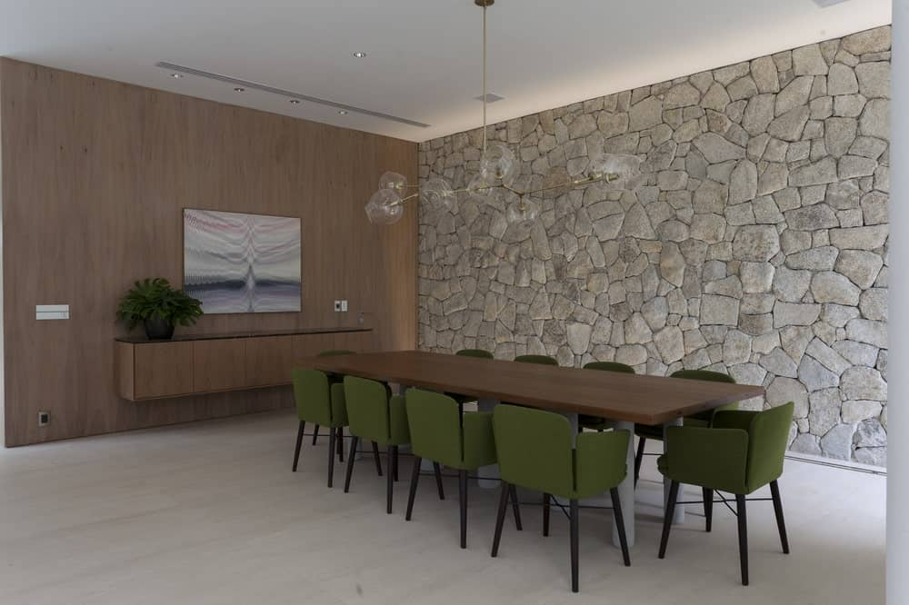 The formal dining room of the house has a simple quality to its large textured wall that makes the long rectangular dark brown wooden table stand out.