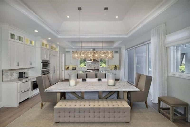 This dining area features a marble top dining table with cozy seats. It also has a glass linear chandelier and a high vaulted ceiling with lights.