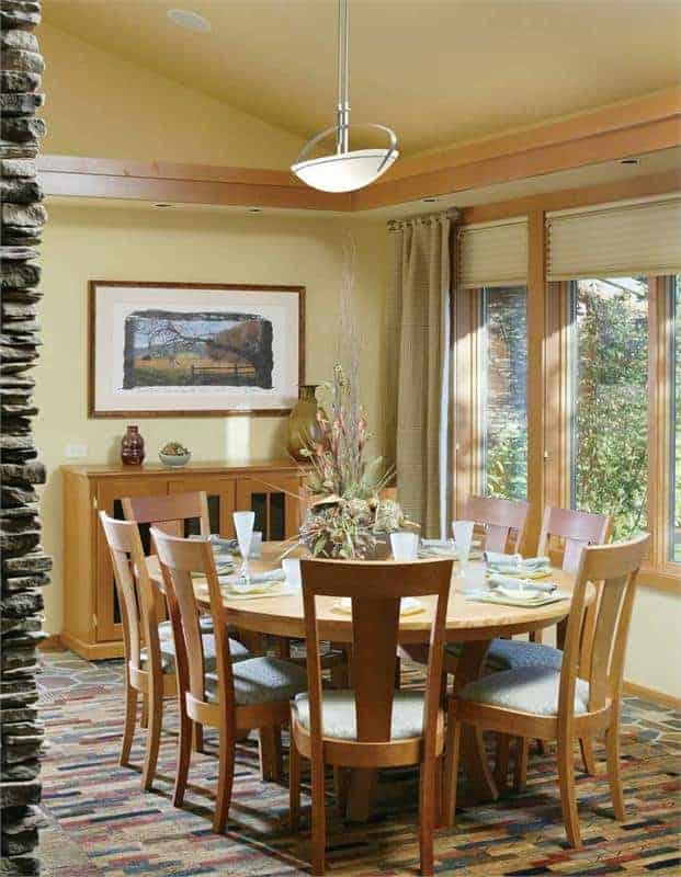 The dining area has a circular wooden dining table set and chairs on the carpet flooring and vaulted ceiling.