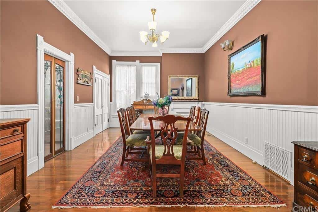 This dining room has a wooden rectangular table and wooden chair on the stylish carpet. It also has a large painting on the wall.