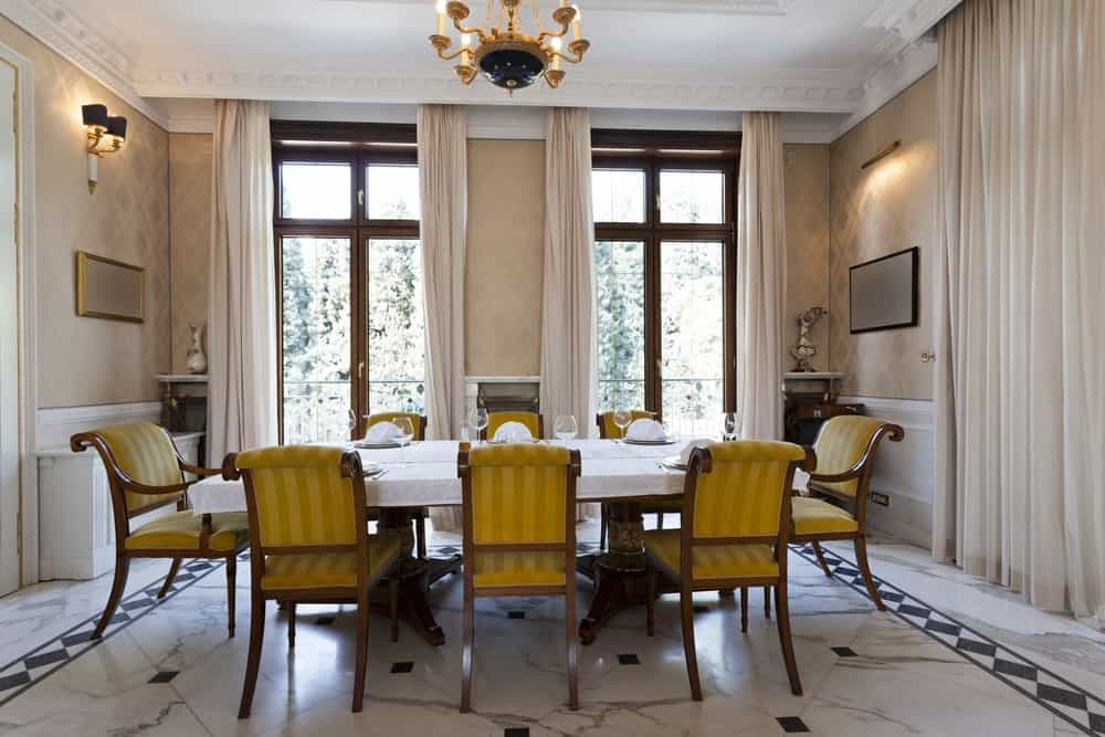 Luxury dining room with ornate ceiling, a chandelier and wall sconces, large windows, and full-height draperies.