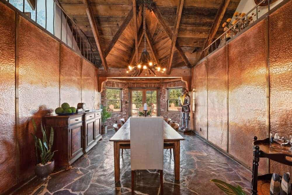 The walls of the dining room are brown wooden that matches well with the rectangular dining table as well as the dining room cabinet on the wall.