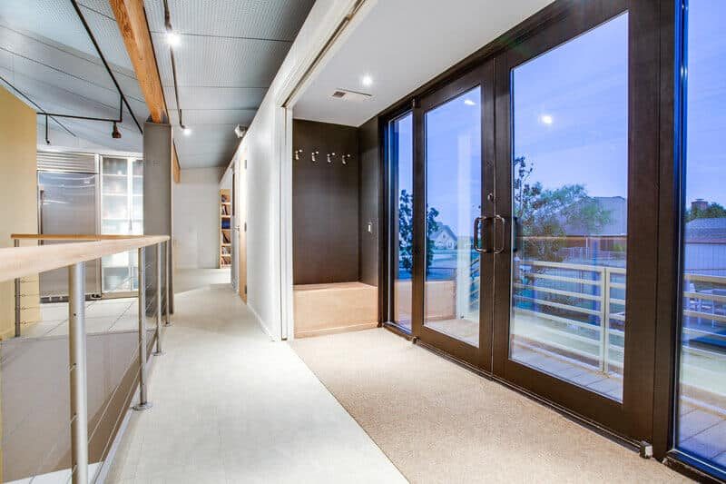 The foyer of the house is located on the second floor. Large windows and massive front doors lend to the open-concept design of the second level and feature a mix of dark wood and the pale oak used throughout the rest of the design.