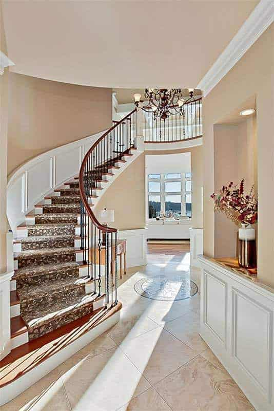 This foyer features an elegant curving staircase with a stunning chandelier that hangs over the marble tiled flooring.