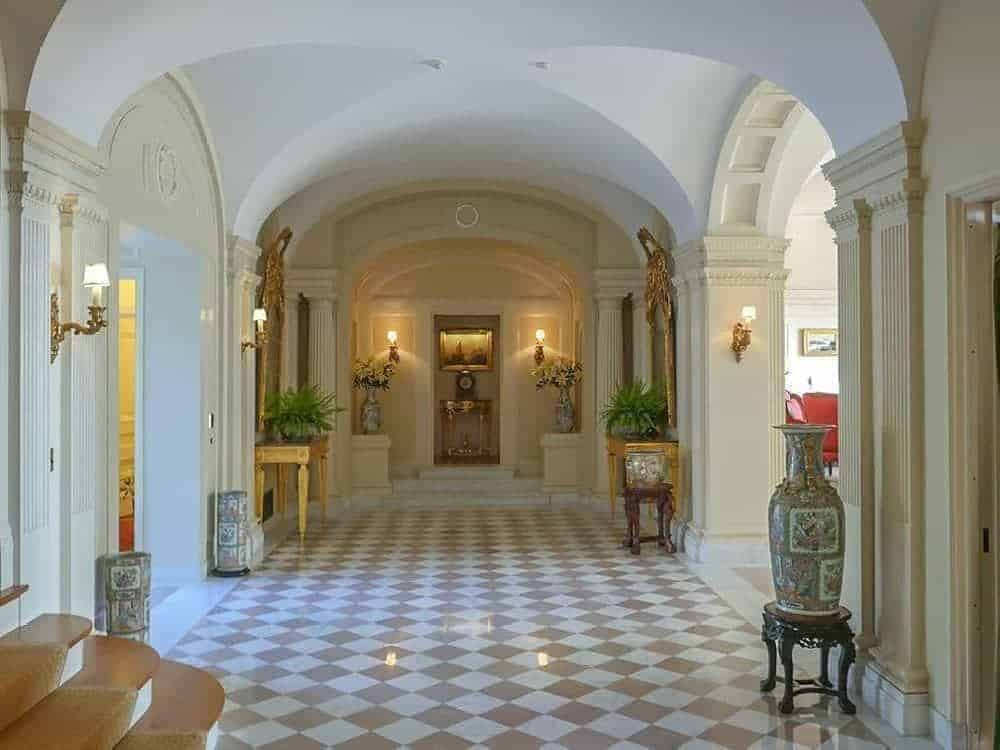 The marble floor of the foyer has a beige and white checkered design that fits quite well with the groin-arched ceiling and arched entryways lining the sides.