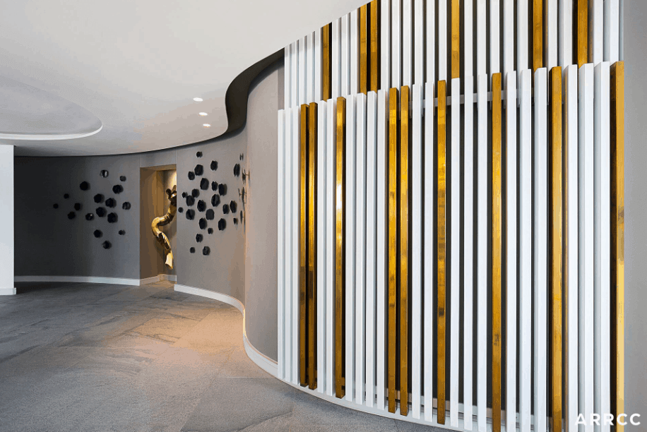 Here's the large hallway in this mansion that leads to other parts of the home. The wall art is definitely interesting with its texture, grey, black, white and gold.