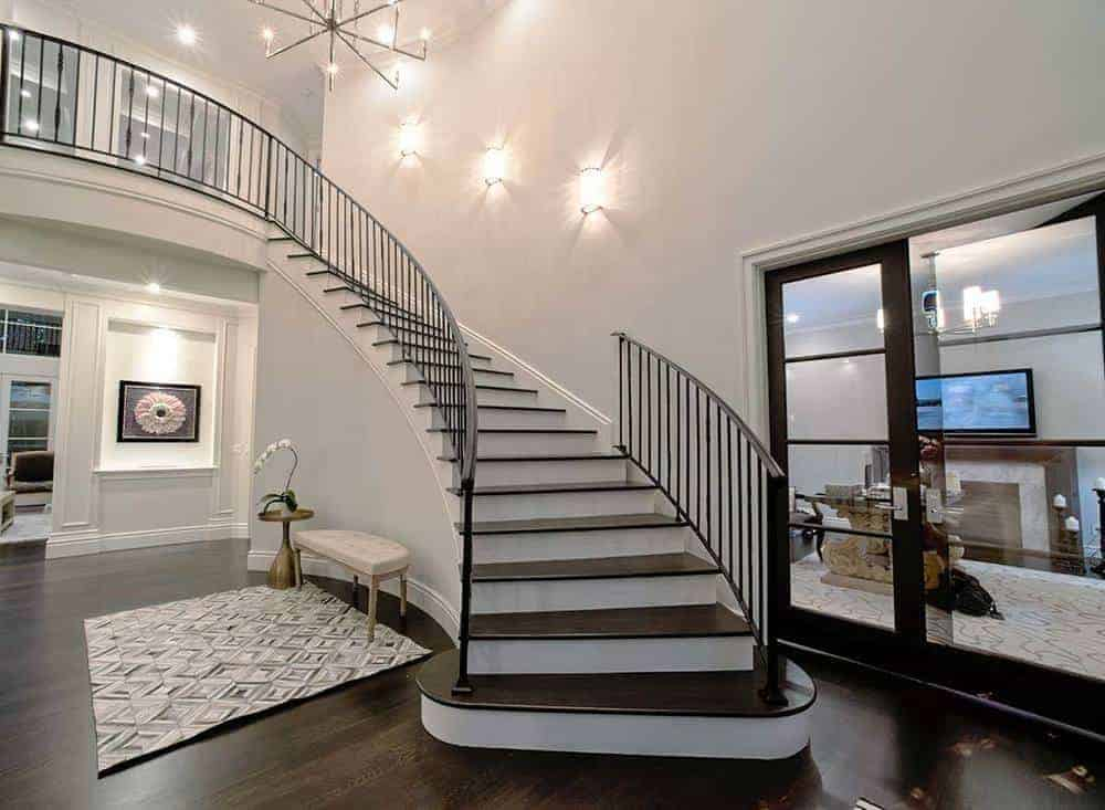 This lobby has a curved staircase with dull wooden strides to coordinate the dim hardwood flooring just as the created iron railings that differentiate the splendid beige dividers.