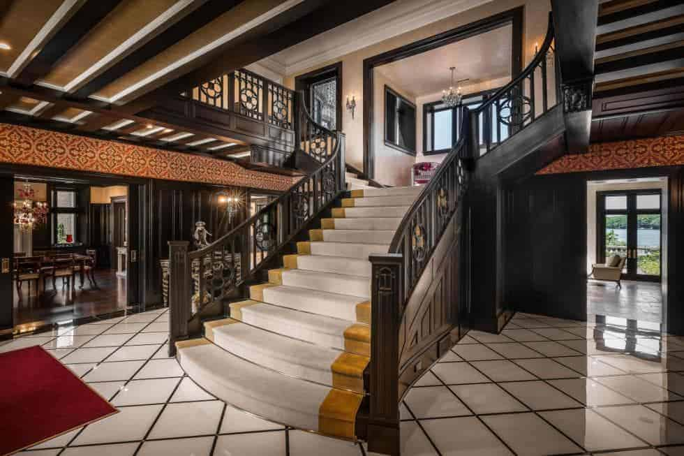 This is the foyer of the mansion that has is opposite the enormous staircase with dim wooden balustrades and fashioned iron railings that contrast the white tiles of the floor.
