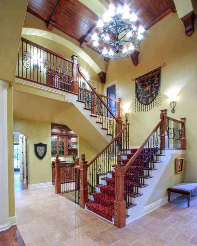 This foyer features a dazzling chandelier that has charming terracotta flooring tiles. This also features a high vaulted ceiling.