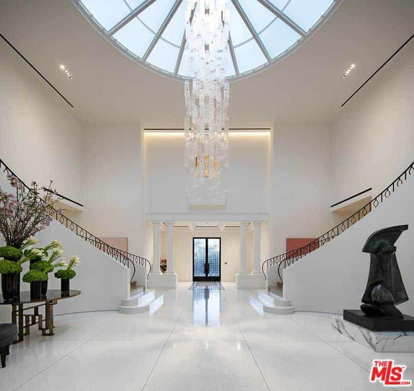 You enter the home in a truly grand white foyer with dome skylight and two winding staircases with wrought iron railings.