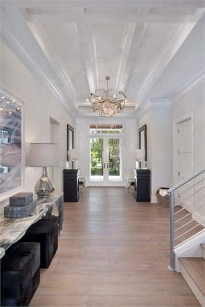 This foyer has a natural hardwood flooring, dark wooden furniture and a beamed ceiling mounted with a gorgeous chandelier.