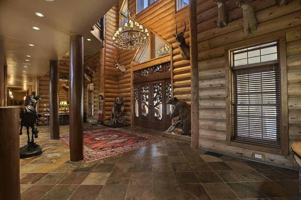 A further view of the foyer shows its large size from its tall ceiling to the floor space dedicated to it adorned with a colorful patterned area rug.