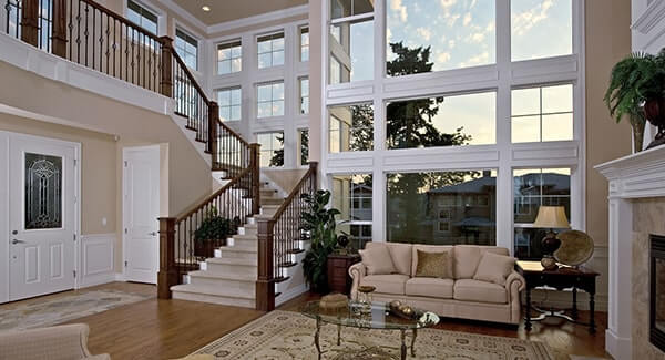 The foyer features a living space with a cozy couch and a round glass table on the rug and a fireplace.