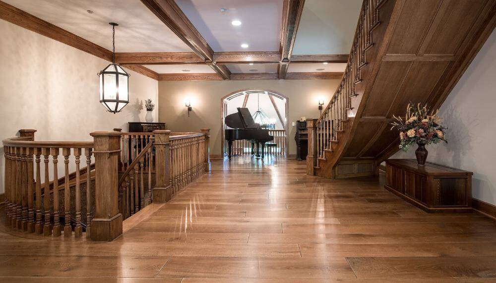 The home's hall boasts hardwood floors, wooden railings, and a gorgeous staircase. This hall also has a black organ in the middle.