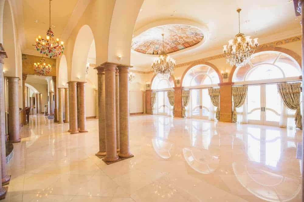 A view of the foyer shows its large size from its tall ceiling with a stunning chandelier and a large hall with tiles flooring.