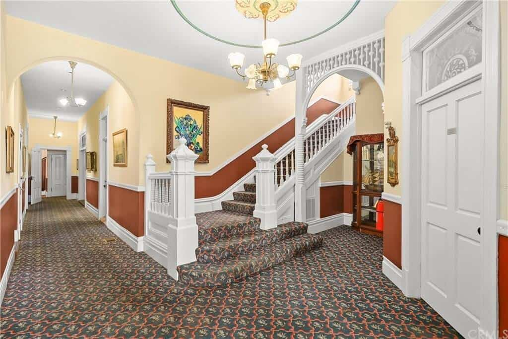 This foyer features gorgeous carpet flooring and attractive walls with wall decors. It also has an impressive chandelier.